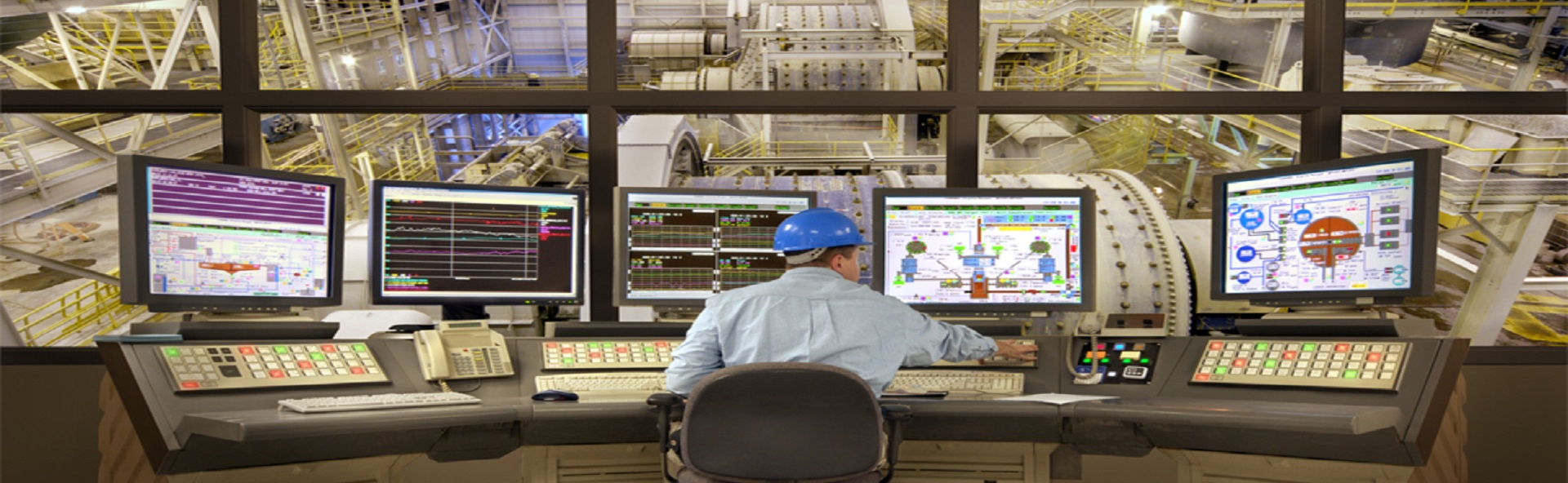 Young man sitting by computers in control room, rear view