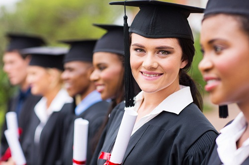 smiling female college graduate standing with friends at graduation